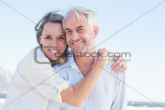 Attractive couple hugging at the beach smiling at camera