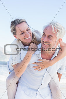 Man giving his smiling wife a piggy back at the beach