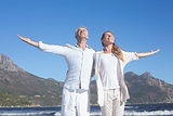 Happy couple standing with arms outstretched at the beach