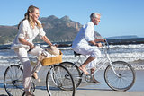 Smiling couple riding their bikes on the beach