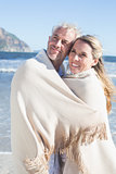 Happy couple wrapped up in blanket on the beach