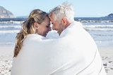 Couple sitting on the beach under blanket smiling at each other