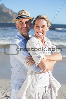 Happy couple standing on the beach together