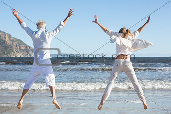 Couple jumping on the beach together