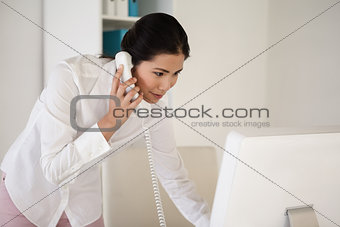Casual asian businesswoman answering the telephone