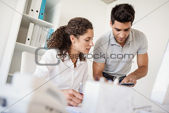 Casual business team looking at calculator together