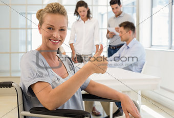 Casual businesswoman in wheelchair smiling at camera with team behind her