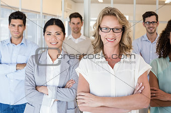 Casual business team smiling at camera with arms crossed