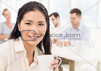 Casual businesswoman smiling at camera during meeting