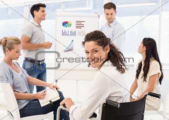 Casual businesswoman in wheelchair smiling at camera during meeting