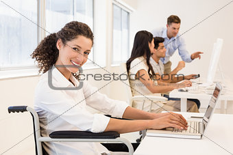 Casual businesswoman in wheelchair smiling at camera