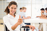 Casual businesswoman in wheelchair smiling at camera giving thumbs up