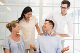 Casual business team congratulating colleague