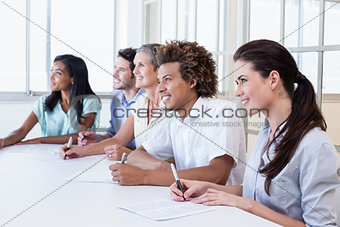 Casual business team taking notes in meeting