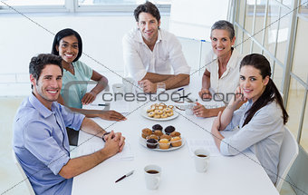 Casual business team having a meeting smiling at camera