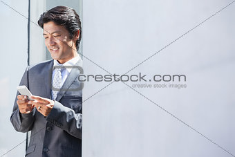 Asian businessman sending text message