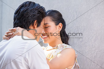 Asian couple embracing and smiling