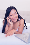 Asian waitress smiling at camera lying on bed talking on phone