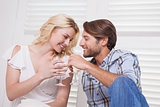 Young couple sitting on floor drinking wine