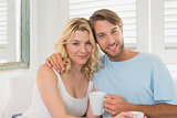 Couple having coffee on the couch smiling at camera
