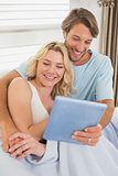 Young couple using tablet pc on the couch