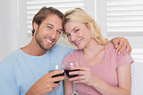 Happy couple having red wine on the couch
