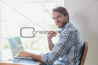 Handsome man sitting at table using laptop