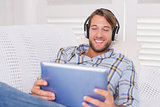 Handsome man lying on couch listening to music on tablet pc