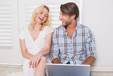 Happy couple sitting on floor using laptop
