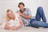 Happy couple sitting on floor doing crossword