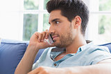 Attractive man making a call on the couch
