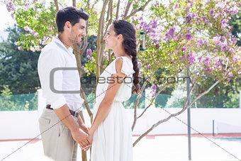 Attractive couple standing in garden holding hands