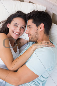 Attractive couple cuddling on bed