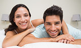 Attractive couple lying on bed smiling at camera