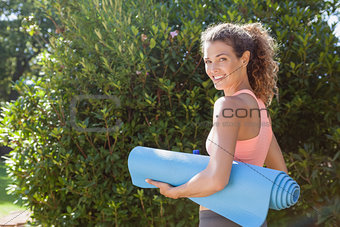 Fit woman holding exercise mat in the park