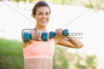 Fit woman exercising with dumbbells in the park