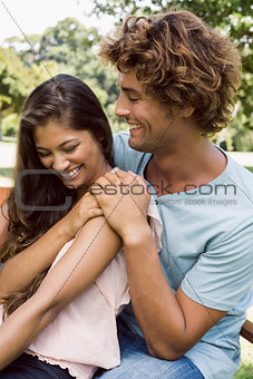 Cute couple laughing and hugging in the park