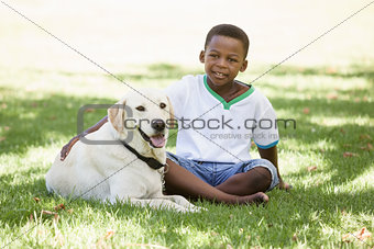 Cute little boy sitting with labrador dog