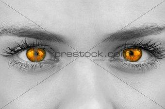 Bright orange eyes on female face