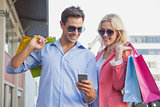 Stylish young couple looking at smartphone holding shopping bags