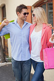 Stylish young couple standing with shopping bags