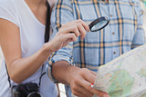 Young tourist couple using magnifying glass on the map