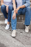 Hip young couple in denim sitting on steps