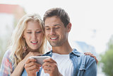 Cute young couple looking at smartphone
