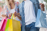Cute young couple holding shopping bags