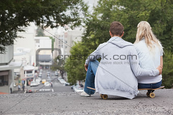 Cute young couple sitting on skateboard