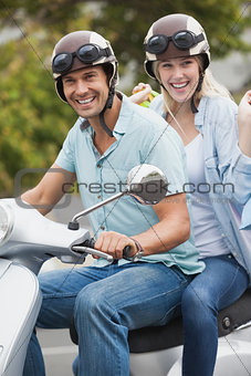Cute young couple riding on scooter