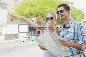 Young tourist couple consulting the map and pointing