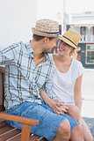 Young hip couple sitting on bench smiling at each other