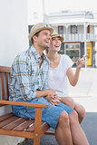 Young hip couple sitting on bench smiling